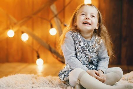 床に座っている金髪の赤ちゃん女の子