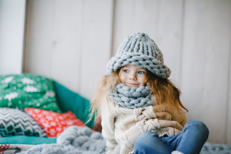 baby girl in knitted hat and scarf Фото со стока