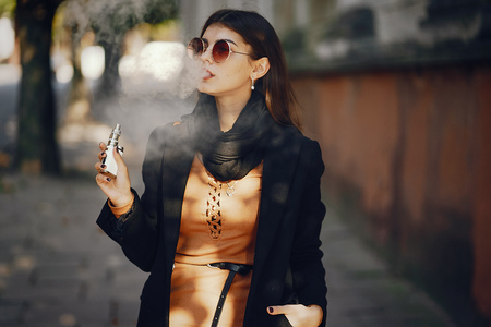 A stylish girl smoking an e-cigarette 스톡 콘텐츠