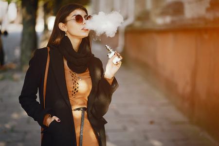電子タバコを吸うスタイリッシュな女の子