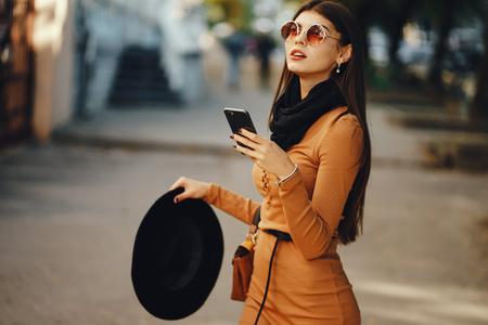 stylish girl walking through the city while using her phone Stockfoto