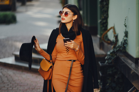 A stylish girl walking through the city while using her phone