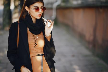 stylish girl smoking an e-cigarette Фото со стока - 99211133