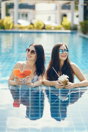 two girls tanning and having fruit by the pool Stock Photo