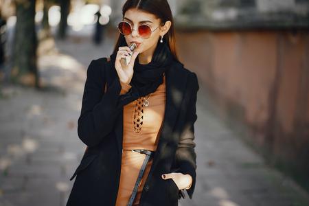 stylish girl smoking an e-cigarette Фото со стока - 101972166