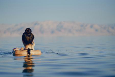 brunette girl swimming in the dead sea Stock Photo