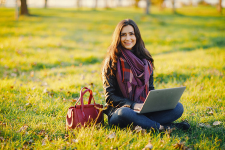 brunette girl working on her laptop in the park