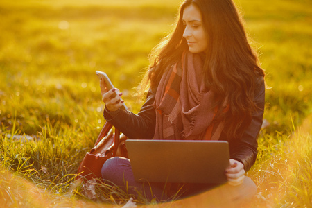brunette girl working on her laptop in the park