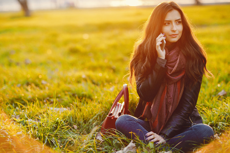 brunette girl using phone while at the park Stock Photo