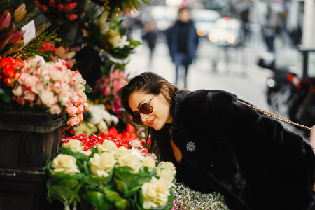 girl stopped to smell the flowers at a market in Paris