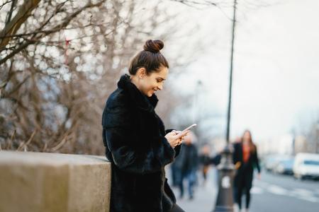 woman using her cell phone while walking through Paris