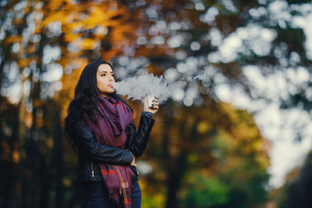 brunette girl is smoking an e-cigarette Фото со стока - 109410624