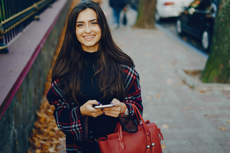 girl using her cell phone while walking through the park Stockfoto