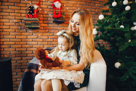 mother and daughter sitting by the christmas tree 版權商用圖片