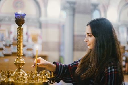 girl lighting a candle in the church Imagens - 113735563