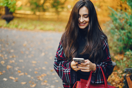girl using her cell phone while walking through the park Stock Photo