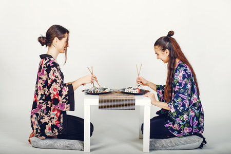 Beautiful girls eating a sushi in a studio Stok Fotoğraf