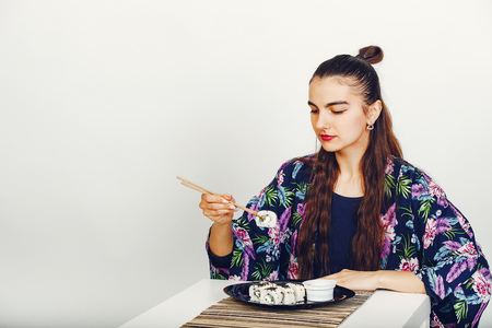 Beautiful girl eating a sushi in a studio