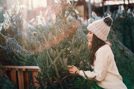 Süße Brünette in einem weißen Pullover mit Weihnachtsbaum Standard-Bild