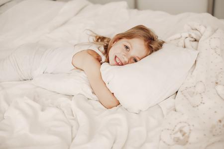 little girl lying in a bad Imagens