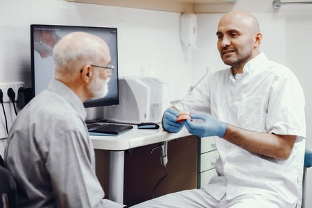 Old man sitting in the dentists office Stock Photo