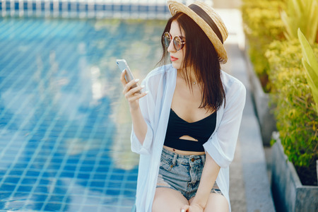 brunette girl using her phone and relaxing by the pool