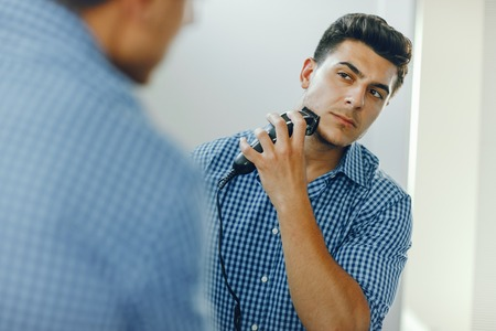 man is shaving his face