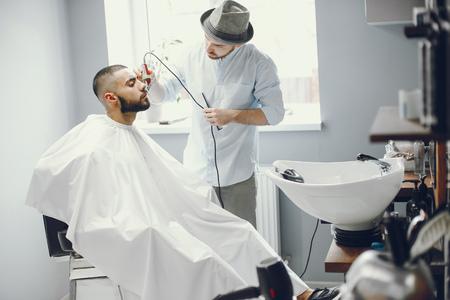 The man cuts his beard in the barbershop.
