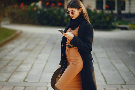 stylish girl walking through the city while using her phone Stock Photo
