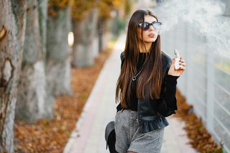 stylish girl smoking an e-cigarette Фото со стока - 118778760