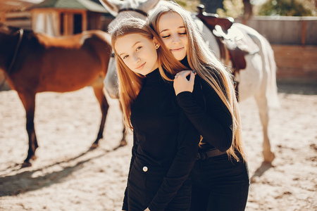 Elegant girls with a horse in a ranch Archivio Fotografico