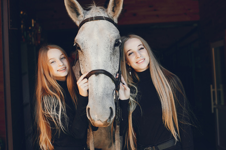 Elegant girls with a horse in a ranch Imagens