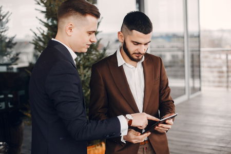 Two businessmen working with a tablet