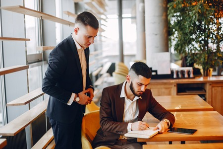 Two businessmen working in a cafe