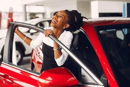 Elegante mujer negra en un salón de autos