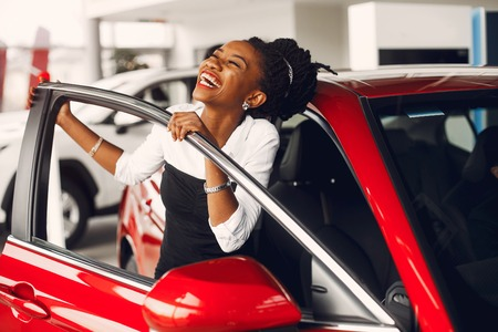 Stylish black woman in a car salon Banque d'images