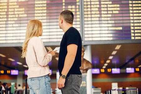Schönes Paar, das in einem Flughafen steht Standard-Bild
