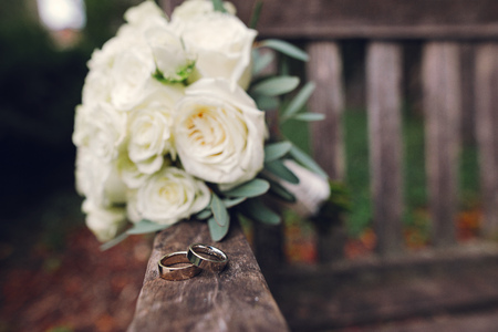 Beautiful wedding bouquet of flowers. White roses on a woodden bench. Two gold rings