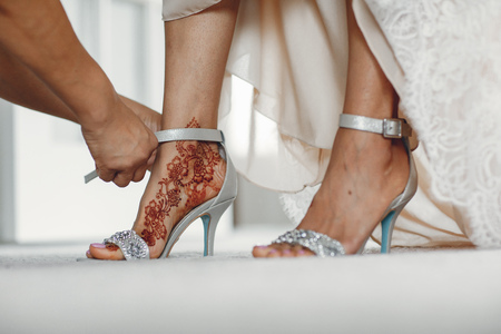 Beautiful bride in a white dress. Woman with gold bracelets. Lady with mehendi on her legs