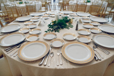 Beautiful wedding decor. Golden dishes in a wedding table