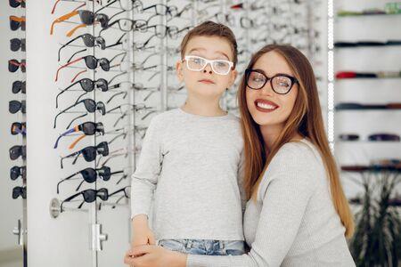Mutter mit kleinem Sohn im Brillenladen Standard-Bild