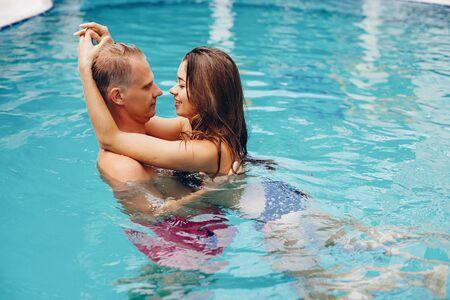 Pareja elegante nadar en la piscina Foto de archivo