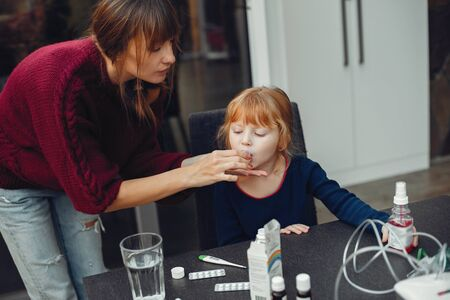 Mother treats her daughter at home Stock Photo - 127252747