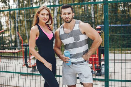 Sports couple in a morning summer park Фото со стока