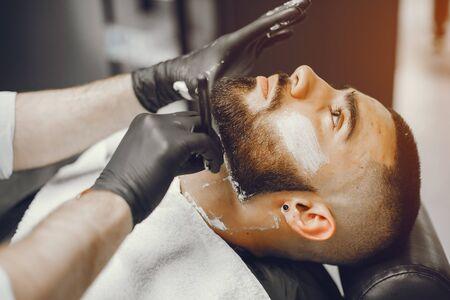 The man cuts his beard in the barbershop Stock Photo