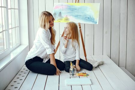 Beautiful mom and daughter are drawing