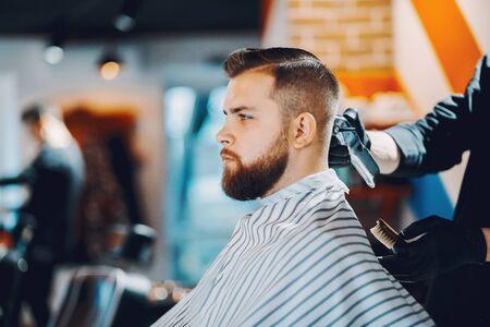 Stijlvolle man zit in een kapperszaak Stockfoto