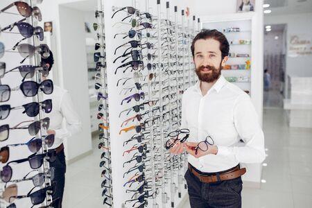 Handsome man in a optics shop Banco de Imagens