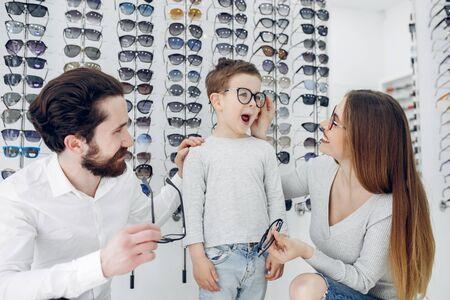 Familia con hijo pequeño en la tienda de gafas Foto de archivo