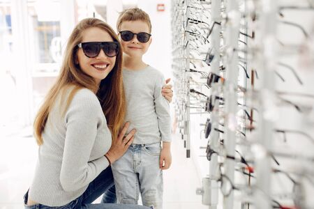 Mother with little son in the glasses store